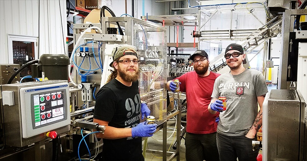 Perrin staffers standing between Cask's mirroed Dual Automated Canning System (ACS) setup
